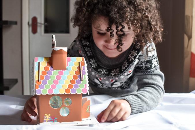 Mädchen bastelt Lebkuchenhaus