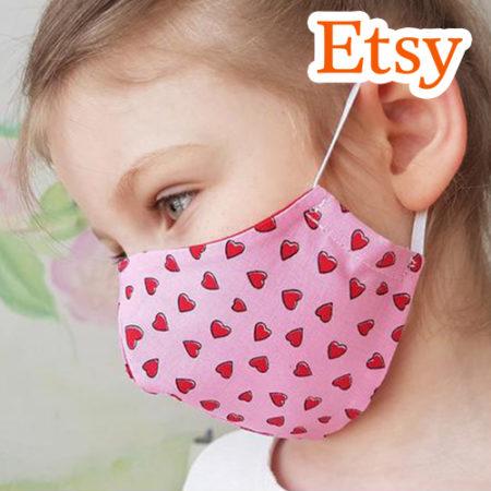 Kind mit Herzchen-Mundschutz
