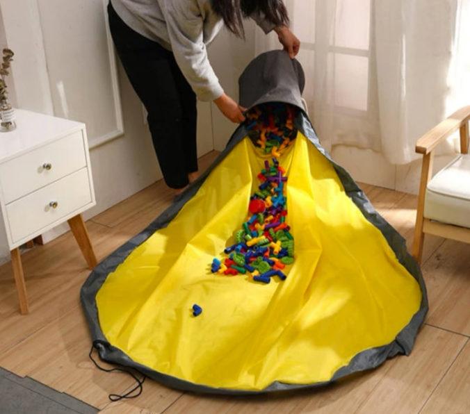 Spielzeuge werden aus einer Ordnungsbox mit integrierter Spieldecke geschüttet