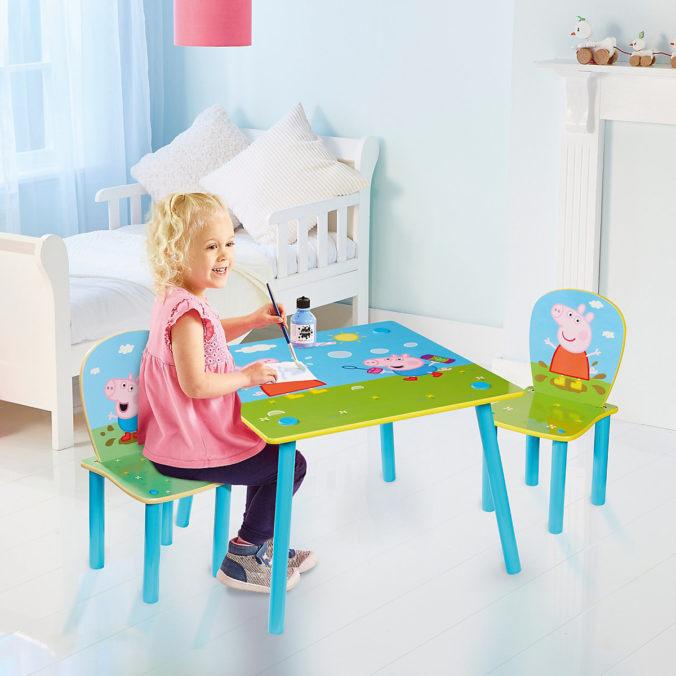 Kind sitzt an Peppa Tisch