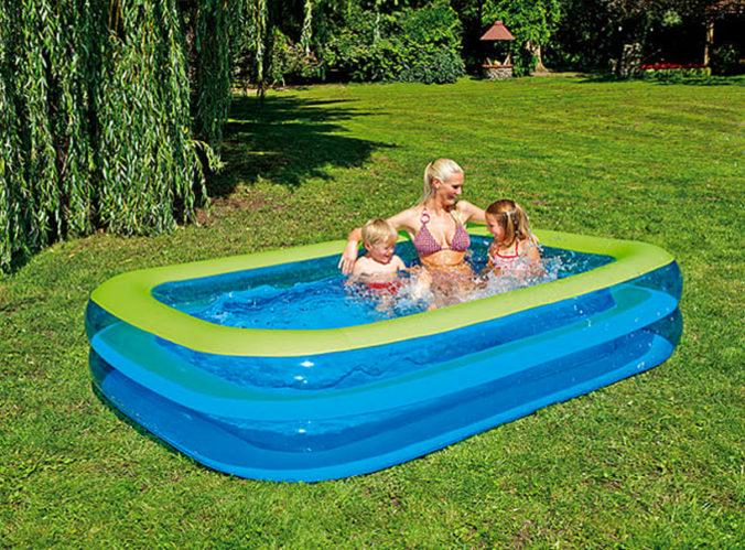 Mutter und Kinder sitzen in aufblasbarem Pool im Garten