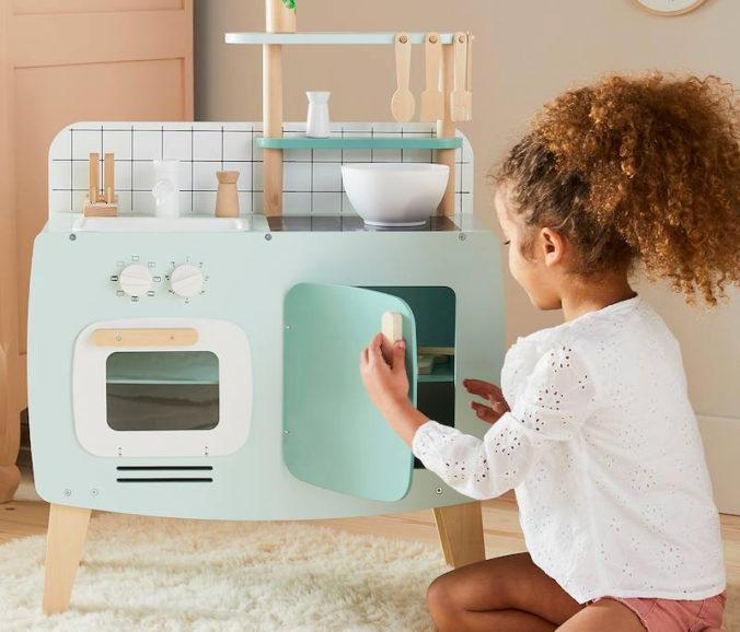 Mädchen spielt mit Spielküche im Retrolook