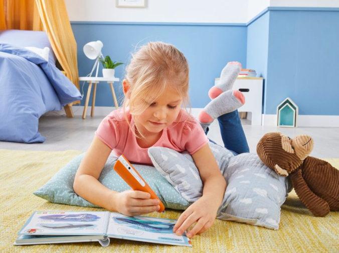 Mädchen spielt mit tiptoi Buch