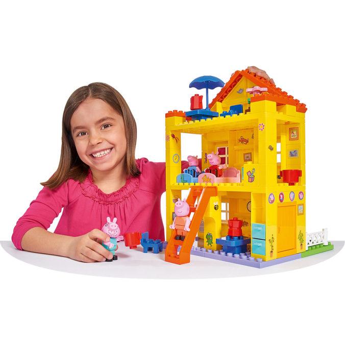 Mädchen spielt mit Peppa Wutz Puppenhaus