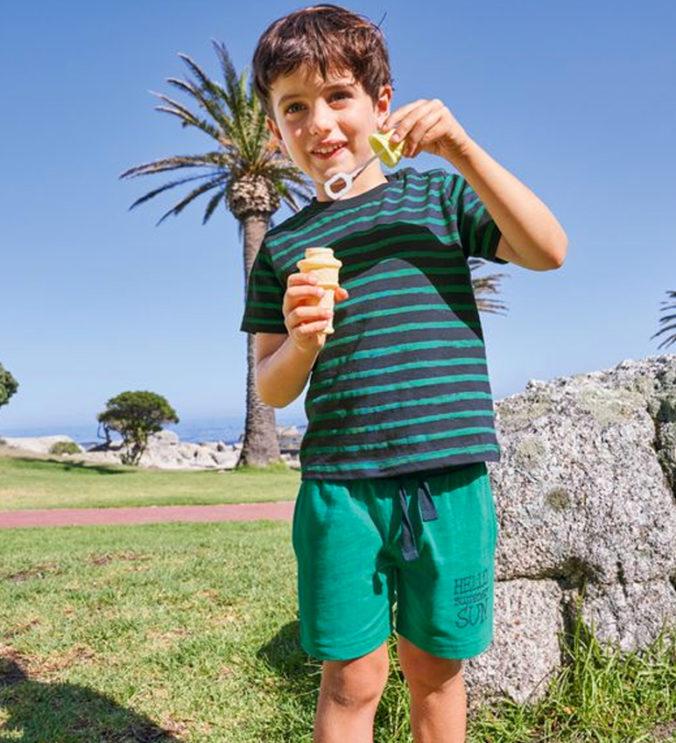 Junge in gestreiftem T-Shirt und grüner Shorts