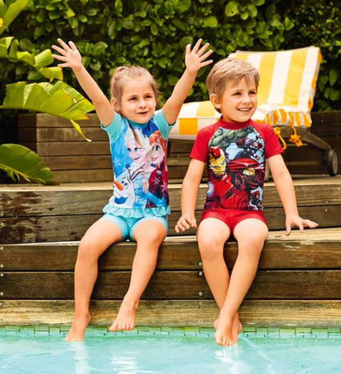 Junge und Mädchen sitzen an einem Pool