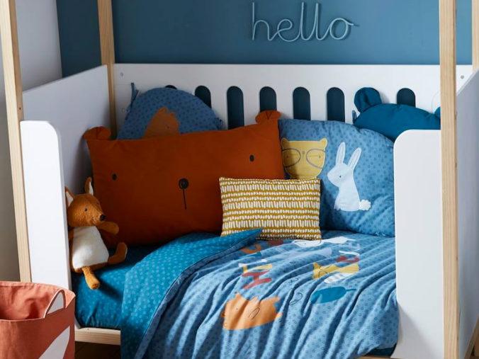 Kinderbett mit blauer Bettwäsche und Bärenkissen