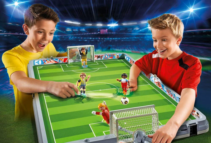 Jungen spielen mit Playmobil Fußball-Arena