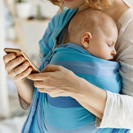 Frau mit Baby in Babytrage