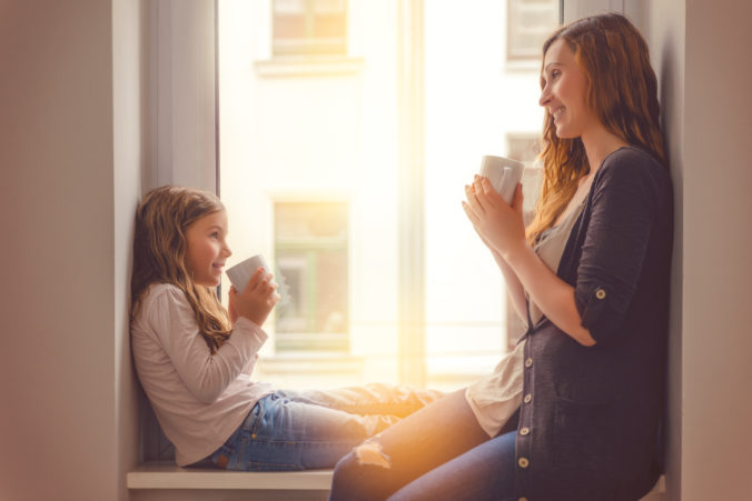 Mama und Kind reden am Fenster