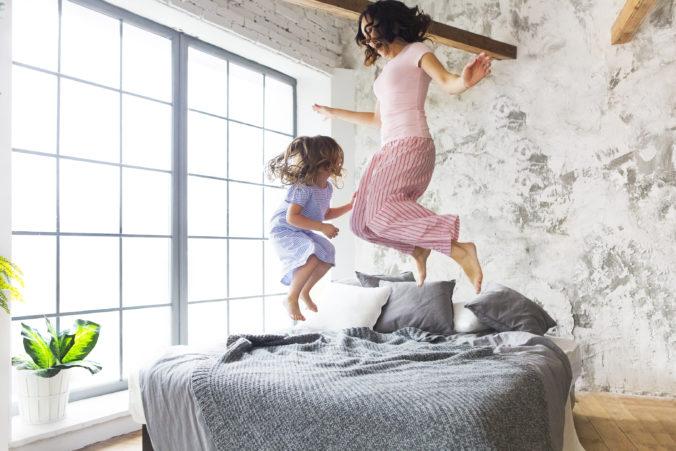 Mama und Kind hüpfen auf dem BEtt