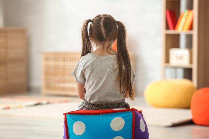 Einsames, kleines Mädchen sitzt mit Rücken zur Kamera