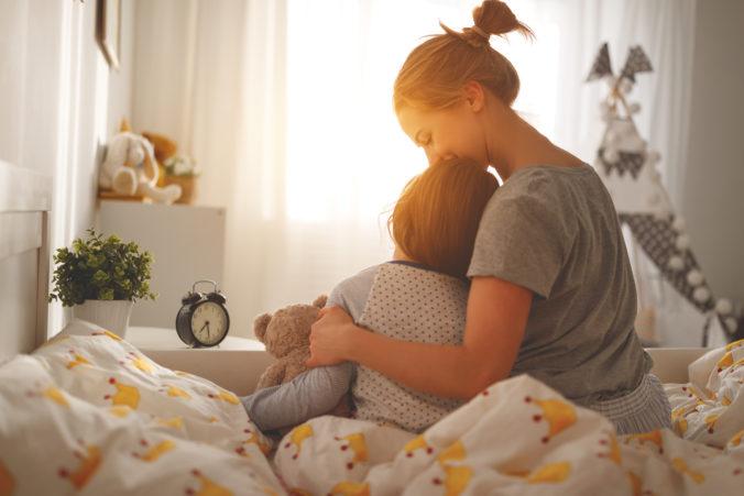 Mama und kleiner Sohn sitzen auf dem Bett