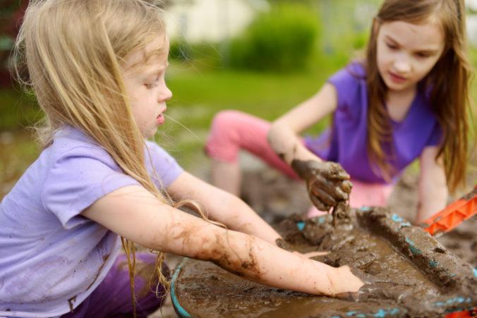 Kleine Mädchen spielen im Matsch