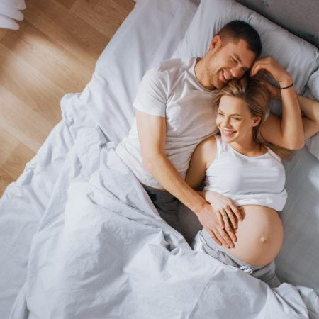 Schwangeres Paar kuschelt im Bett