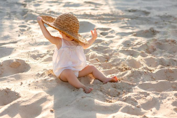 Baby sitzt mit Hut am Strand