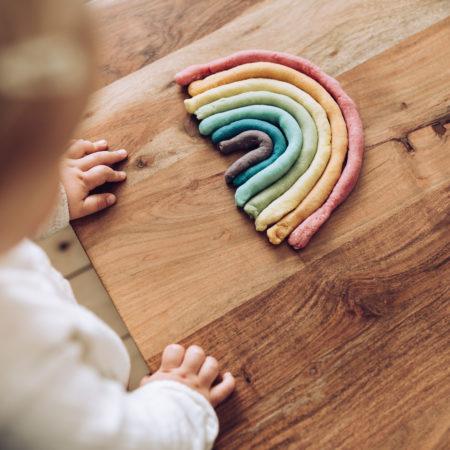 Kleinkind knetet bunten Regenbogen auf Holztisch