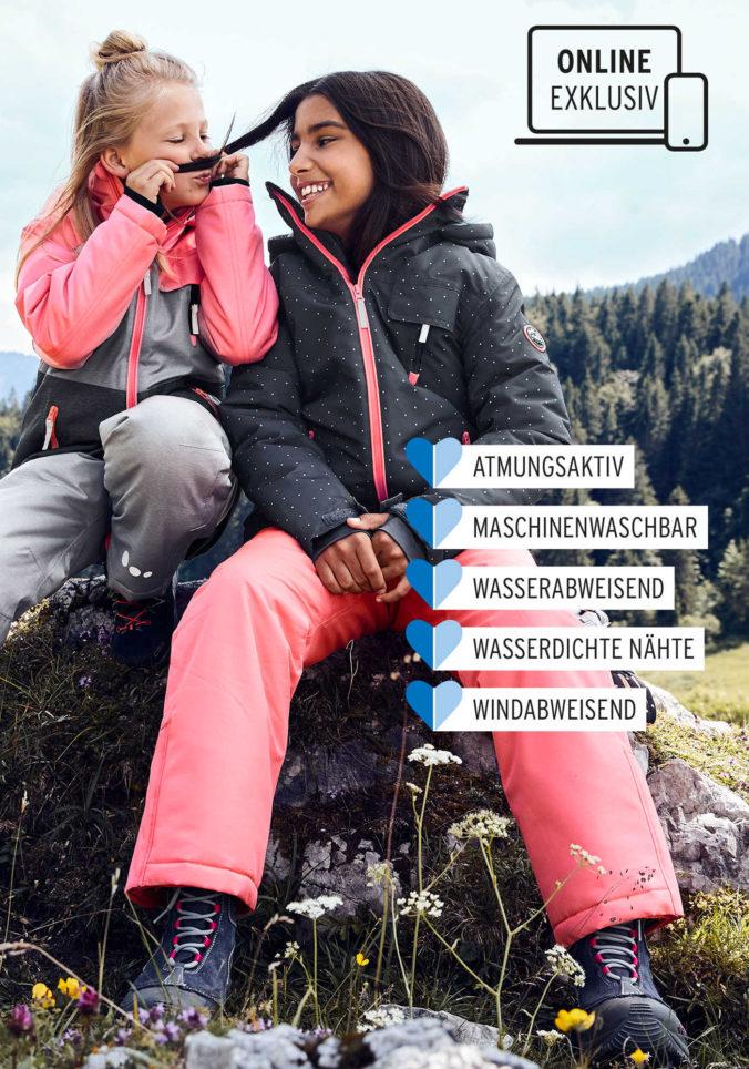 Mädchen in Schneekleidung sitzen auf einem Stein