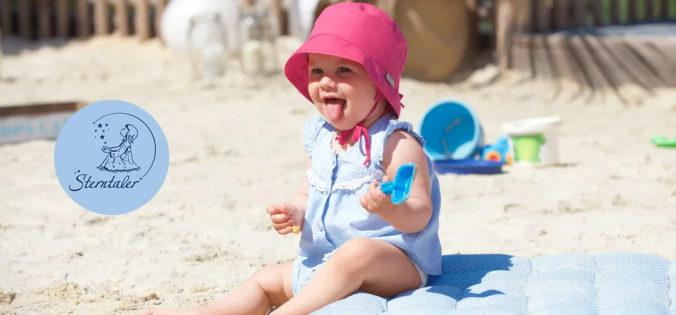 Baby sitzt am Strand