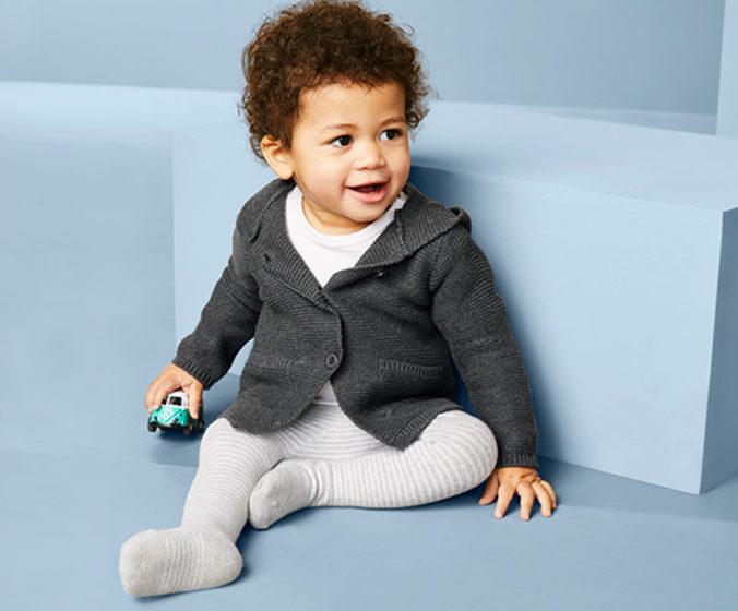 Baby in grauer Strickjacke