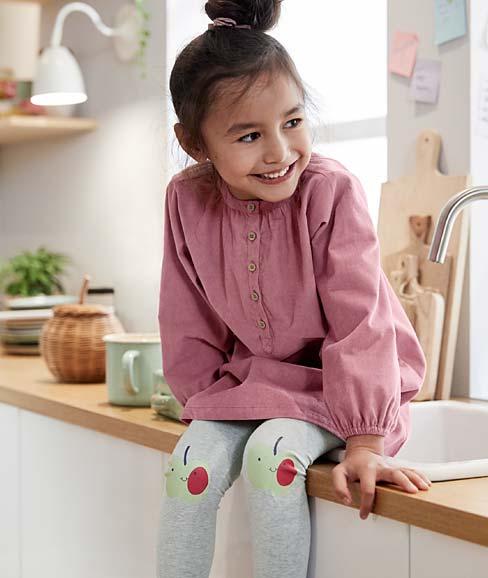 Kleinkind sitzt auf Küchenzeile