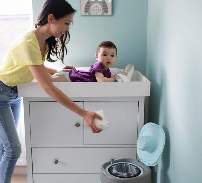 Mutter mit Baby schmeißt Windel in Windeleimer