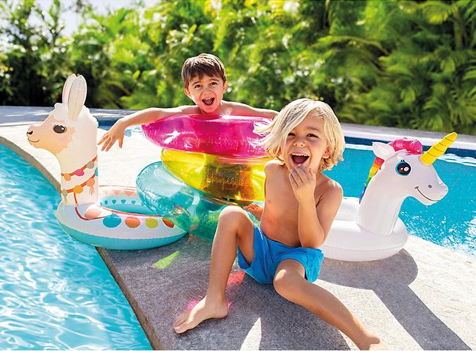Kleine Jungs mit Schwimmringen im Einhorn- und Lama Design