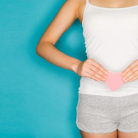 Frau hält rosa Papierherz vor dem Bauch