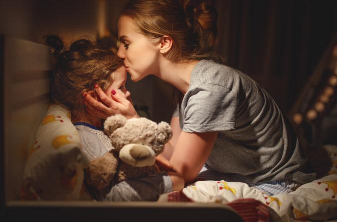 Mutter küsst kleine Tochter auf die Stirn