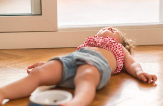 trotziges Kind liegt weinend auf dem Boden
