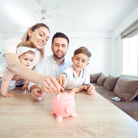 Familie steckt Münzen ins Sparschwein