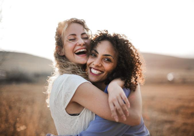 Zwei Frauen umarmen sich und lachen