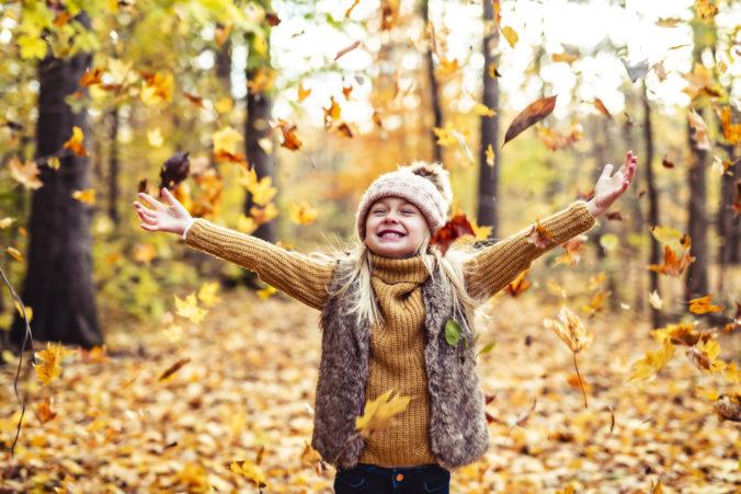 Kind schmeißt herbstblätter in die Luft