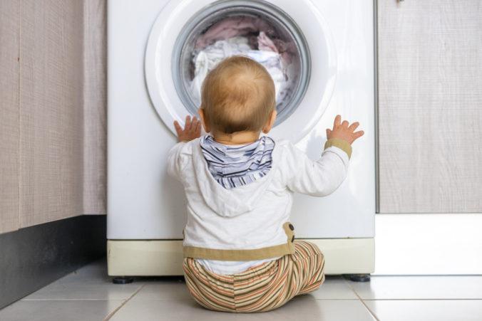 Baby sitzt vor Waschmaschine