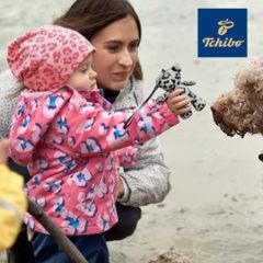 Mutter und Kind spielen mit Hund am Strand