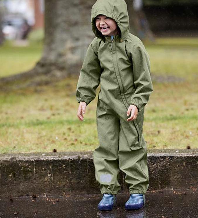 Kind im Regenanzug spielt in Pfütze