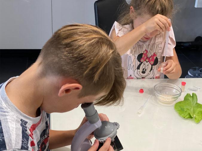 Kinder spielen mit einem Mikroskop