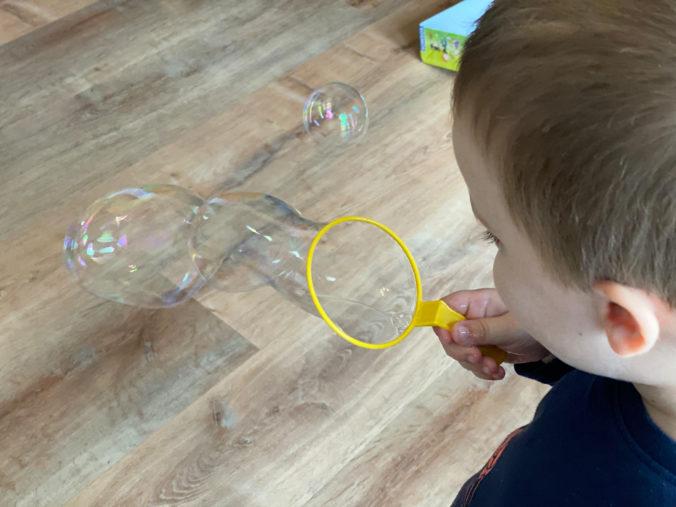 Kleinkind macht Seifenblasen mit Seifenblasenring