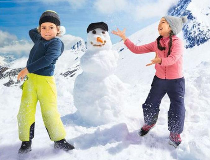 Kinder bauen einen Schneemann