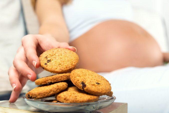 Schwangere isst Keks im Bett