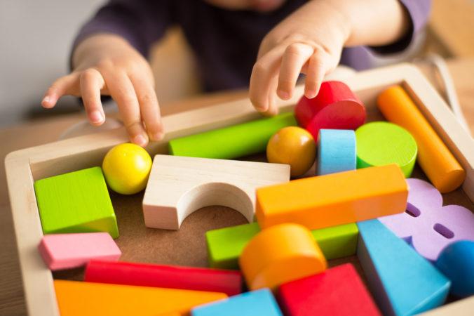 Kinderhand greift nach Spielklötzen