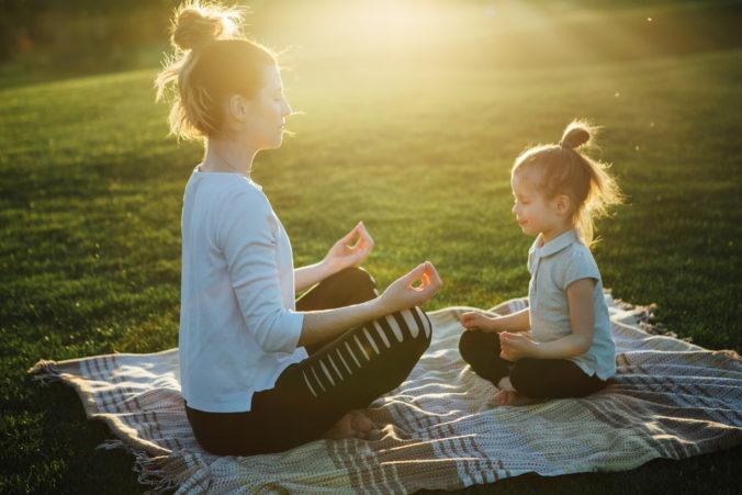 Mama und kleine Tochter meditieren im Park bei Sonnenaufgang