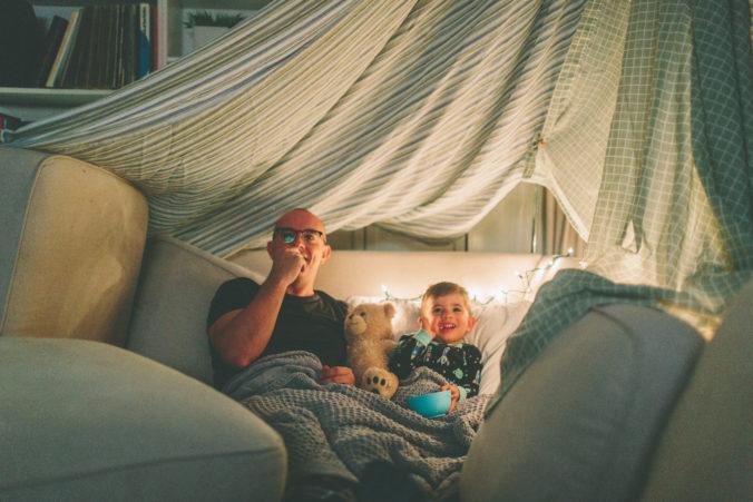 Papa und Kind schauen Fernsehen unter Deckenhöhle