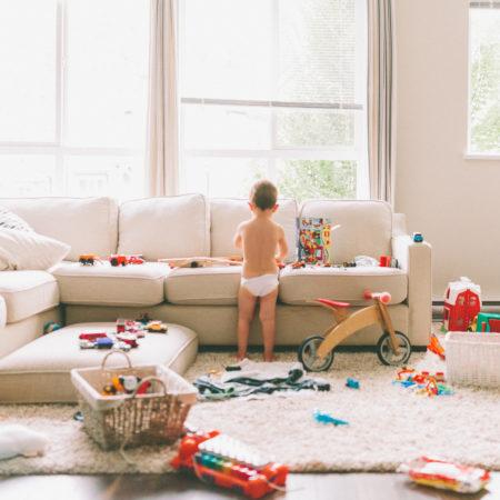 Kind umgeben von sehr viel Spielzeug