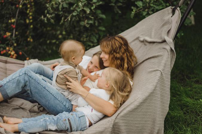 Mama und Kinder liegen zusammen in der Hängematte