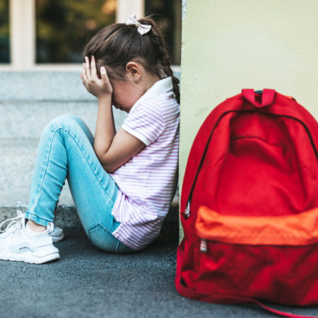 Kind sitzt traurig an der Wand