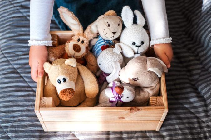 KInderhände greifen an Kiste voll mit Kuscheltieren