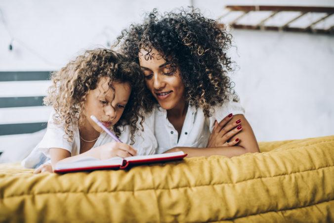 Mama und Kind liegen zusammen im BEtt und schreiben etwas in ein Buch
