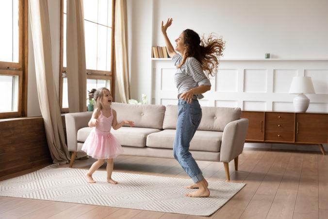 Kind und Mama tanzen im Wohnzimmer