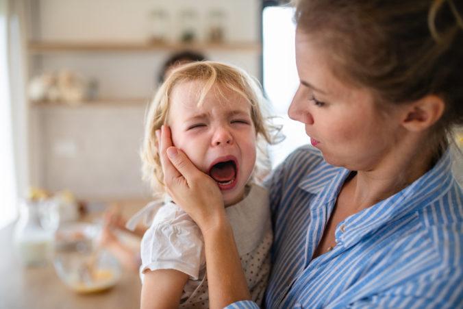 Kind auf dem Arm der Mutter weint